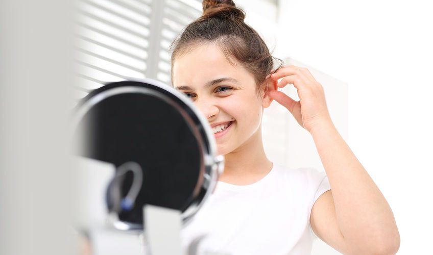 young woman inserting a hearing aid while looking in small mirror, NHHI hearing aids in New England